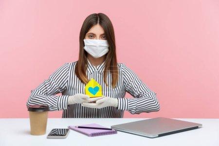 Photo pour Location pendant la quarantaine pour coronavirus. Agence immobilière femme assise sur le lieu de travail, portant un masque hygiénique et des gants de protection, tenant une maison en papier, offrant de l'aide en matière d'hypothèques, assurance habitation - image libre de droit