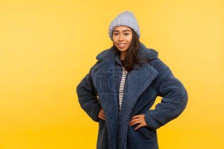 Photo pour Portrait de joyeuse fille heureuse portant un chapeau d'hiver chaud et manteau de fourrure souriant joyeusement, modèle de mode glamour dans une tenue urbaine élégante posant à la caméra. studio intérieur tourné isolé sur fond jaune - image libre de droit