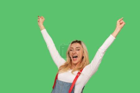 Photo pour Oui, je suis gagnant ! Portrait de femme adulte enthousiaste en combinaison de denim élégant criant hourra et gardant les mains en l'air, se réjouissant de la victoire, la réalisation de l'objectif. studio tourné isolé sur fond vert - image libre de droit