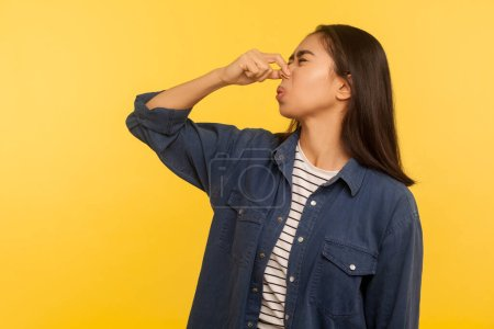 Photo for Awful smell! Portrait of girl in denim shirt grimacing in disgust and holding breath, grabbing nose with fingers, avoiding stinky odor, fart gases. indoor studio shot isolated on yellow background - Royalty Free Image