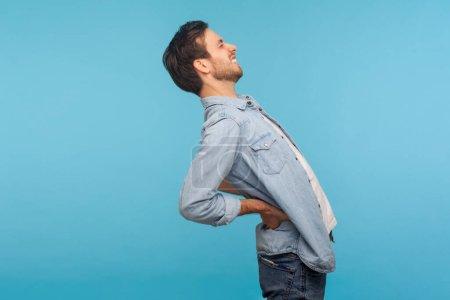 Photo pour Vue latérale, travailleur fatigué en chemise en jean souffrant de maux de dos, d'inconfort lombaire inférieur, de spasme musculaire douloureux, de polyarthrite rhumatoïde ou de nerf pincé. studio intérieur tourné isolé sur fond bleu - image libre de droit