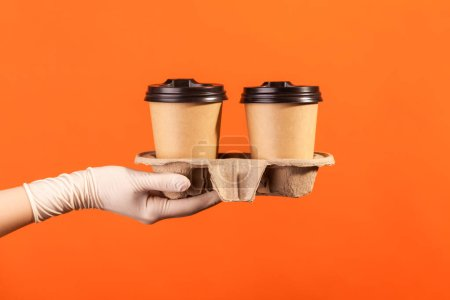 Photo for Profile side view closeup of human hand in white surgical gloves holding and showing cup of hot takeaway mug drink in hand. indoor, studio shot, isolated on orange background. - Royalty Free Image