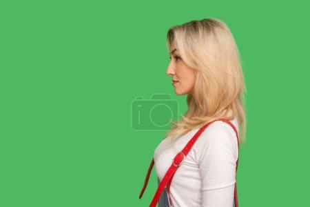 Photo pour Vue latérale de la femme adulte concentrée sérieuse avec les cheveux blonds dans des combinaisons élégantes regardant l'espace de copie avec l'expression concentrée calme visage coûteux. studio intérieur tourné isolé sur fond vert - image libre de droit