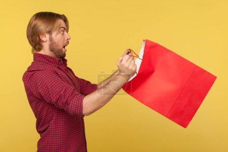 Photo pour Effrayé acheteur surpris gars en chemise à carreaux regardant à l'intérieur sac à provisions avec de grands yeux bouche ouverte dans l'étonnement, choqué par l'achat. studio intérieur isolé sur fond jaune, vue latérale - image libre de droit