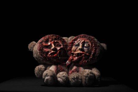 Photo pour Jouet d'Halloween. porte des jumeaux siamois. sur fond noir. visages coupés sont des crânes visibles. taché de sang - image libre de droit