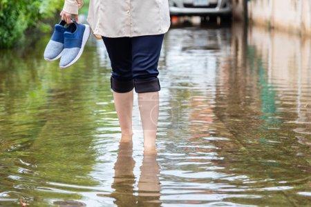 Photo pour Femme marchant sur la route d'inondation avec des chaussures de maintien après les fortes pluies, cause de démangeaisons de la peau comprennent, attention à la leptospirose, il peut être infecté par contact avec l'eau, le pied des athlètes, tinea pedis - image libre de droit