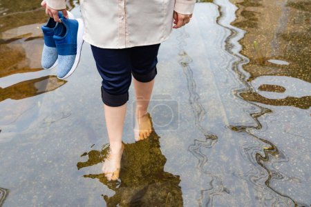 Photo pour Femme marchant sur la route d'inondation avec des chaussures de maintien après les fortes pluies, la cause des démangeaisons de la peau comprennent, attention à la leptospirose, il peut être infecté par contact avec de l'eau, le pied des athlètes ou tinea pedis - image libre de droit