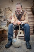 wicker craftsman working on glass bottle in the foregroun