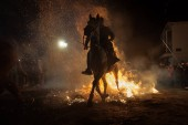 Horse passing over the bonfire, as a tradition to purify the soul of animals, in the celebration carried out in the town of San Bartolom de Pinares, province of Avila, Spain, on January
