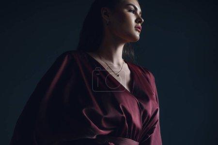 Jeune fille élégante en robe bordeaux. Portrait beauté