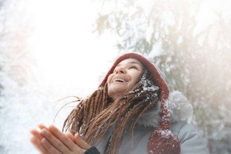 Photo pour Jeune fille se réjouit des chutes de neige dans la forêt. Concept positif et style de vie - image libre de droit