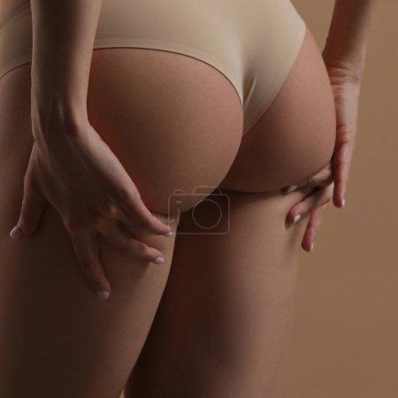 Photo pour Skinny jeune femme en lingerie soulève ses fesses avec ses mains. Vue arrière sur fond beige. Fitness, alimentation, soins de la peau et du corps - image libre de droit