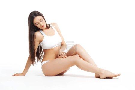 Photo pour Mince jeune femme assise en sous-vêtements sur fond blanc. Dépilation, rasage, soin de la peau sur les jambes - image libre de droit
