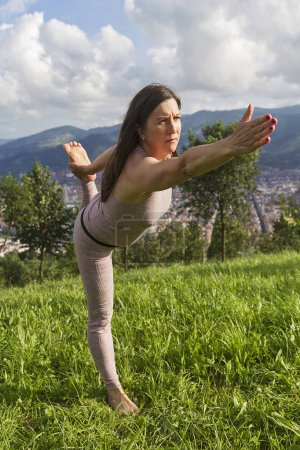 A woman practicing yoga in a park...