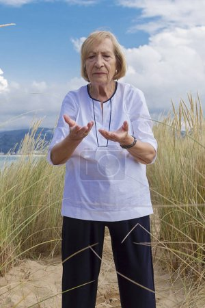 A senior woman practicing Tai Chi in a beach...