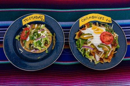Photo pour Vue rapprochée et à angle élevé de deux plats, contenant des tostadas et des chilaquiles, des aliments mexicains servis dans un stand de vente d'aliments de hoot lors d'une foire alimentaire locale . - image libre de droit