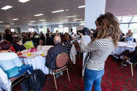 Photo pour Une photographe féminine est vue prenant des photographies pendant une assemblée professionnelle dans une grande salle, des collègues se rassemblent pour l'événement d'entreprise. - image libre de droit