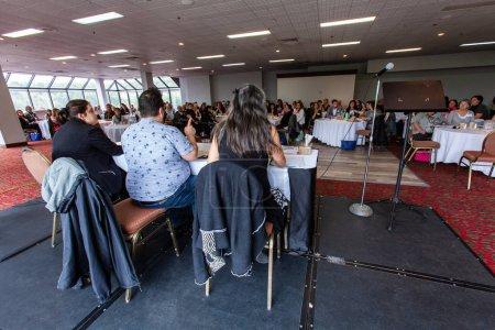 Photo pour Trois haut-parleurs sont vus par derrière, assis à l'avant d'une grande salle remplie de gens d'un environnement d'entreprise, présentation professionnelle. - image libre de droit