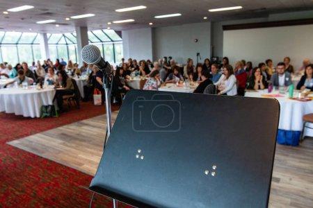 Photo pour Le stand d'un orateur avec le microphone est vu de près pendant une conférence emballée pour des personnes professionnelles, les employés flous sont vus s'asseyant derrière. - image libre de droit
