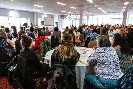 Photo pour Une vue arrière sur un groupe de femmes s'asseyant à une grande table pendant un événement de réseautage pour des ouvriers blancs de collier. Beaucoup de gens peuvent être vus en regardant une présentation - image libre de droit
