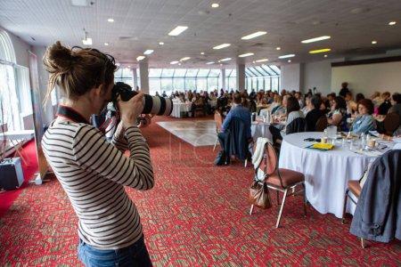 Photo pour Une vue au-dessus de l'épaule d'une femme prenant la photo pendant une assemblée générale, les personnes floues assises aux tables sont vues à l'arrière-plan avec l'espace de copie - image libre de droit