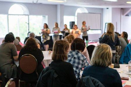 Photo pour Une vue arrière d'un public regarder un groupe de femmes professionnelles se tenir sur scène et donner une présentation. Les gens regardent et apprennent de leurs collègues. - image libre de droit