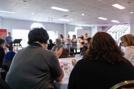 Photo pour Une vue de près vers le haut de deux personnes potelues s'asseyant à une table pendant une journée de formation de lieu de travail, des haut-parleurs flous peuvent être vus sur l'étape à l'arrière-plan. - image libre de droit
