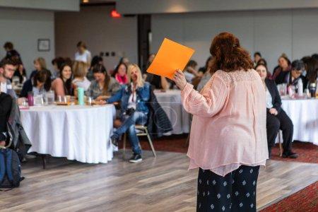 Photo pour Un directeur de bureau potelé est vu debout et parlant à une salle bondée d'employés, elle tient une feuille orange dans l'air et, avec l'espace de copie sur la gauche. - image libre de droit