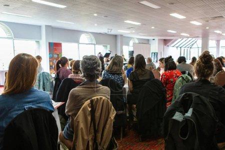 Photo pour Une vue générale sur une salle bondée de travailleurs réunis pour un événement professionnel à l'intérieur d'une grande salle, plus de vingt personnes regardent une présentation. - image libre de droit