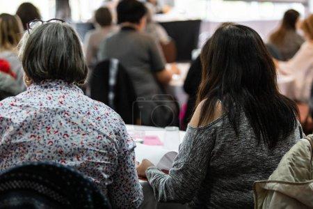 Photo pour Un plan rapproché et une vue arrière de deux femmes s'asseyant à une table pendant une assemblée générale, on tourne des pages pour lire des notes pendant qu'elle regarde vers la scène. - image libre de droit