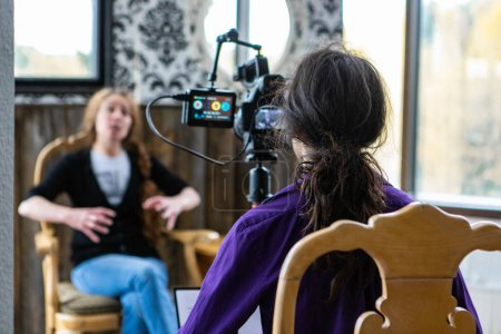 Photo pour Une vue au-dessus de l'épaule d'un vidéaste filmant une dame parlant pendant un événement professionnel. Collègue féminin parlant de l'autonomisation dans le lieu de travail - image libre de droit