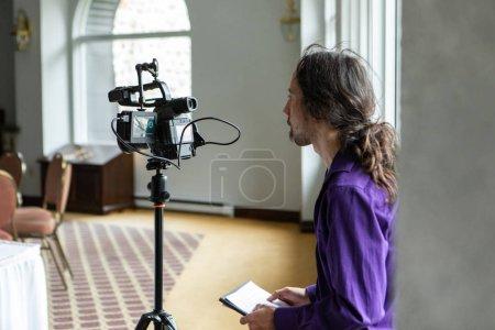 Photo pour Une vue de profil secondaire d'un cinéaste professionnel travaillant derrière une caméra pendant une assemblée générale, filmant des événements et des personnes pendant la journée, avec la pièce pour la copie - image libre de droit