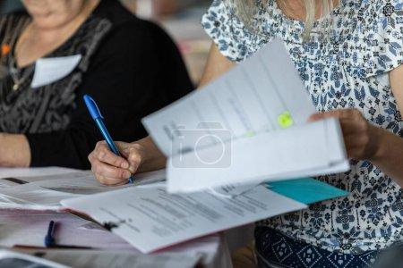Photo pour Une vue de plan rapproché d'une femme caucasienne lisant des papiers pendant un événement professionnel pour des collègues, elle emploie un stylo pour prendre des notes, avec l'espace de copie sur la gauche. - image libre de droit