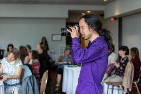 Photo pour Une vue de profil secondaire d'un homme caucasien utilisant une chemise pourpre et prenant des photos pendant un événement de formation pour une grande corporation, avec l'espace de copie sur la gauche - image libre de droit