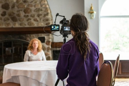 Photo pour Une vue arrière d'un vidéaste professionnel filmant une femme caucasienne parlent de l'égalité dans le lieu de travail pendant un événement de collaboration pour des employés. - image libre de droit
