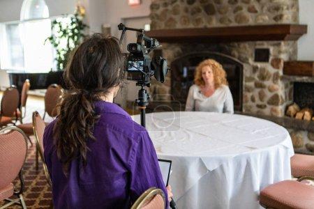 Photo pour Une vue au-dessus de l'épaule d'un homme utilisant l'équipement professionnel d'enregistrement pour filmer une dame pendant un événement professionnel de carrière pour des ouvriers blancs - image libre de droit