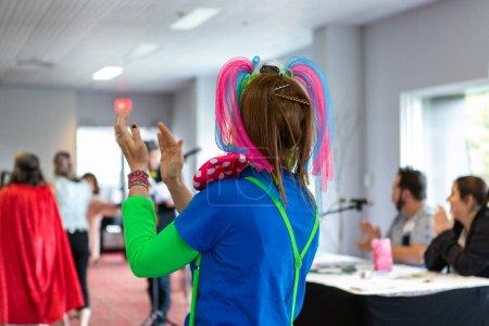 Photo pour Les employés sont vus par derrière, vêtus de costumes vibrants et dansant lors d'un exercice de renforcement de l'équipe lors d'un événement de formation pour une grande organisation. - image libre de droit