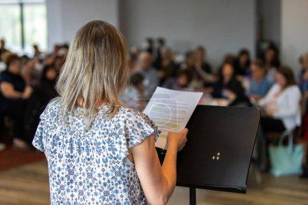 Photo pour Une vue au-dessus de l'épaule d'un orateur plaçant un discours sur un podium pendant une grande réunion des ouvriers de bureau. Des collègues flous sont vus en arrière-plan. - image libre de droit