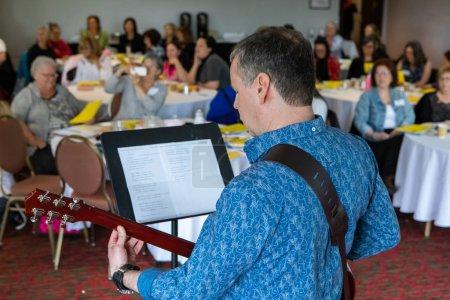 Photo pour Une vue au-dessus de l'épaule d'un homme jouant une guitare pendant une assemblée générale, il divertit des participants pendant l'événement, avec l'espace de copie sur la gauche. - image libre de droit