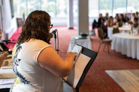 Photo pour Une vue de profil de côté d'une femme caucasienne utilisant un dessus blanc et parlant par un microphone pendant un événement pour des ouvriers de bureau, les papiers sont vus sur le lutrin. - image libre de droit