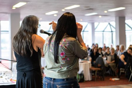 Photo pour Une vue arrière de deux collègues féminines, debout devant une salle pleine de collègues de travail et parlant de l'autonomisation et de l'égalité sur le lieu de travail. - image libre de droit