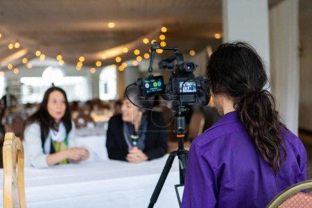 Photo pour Une vue rapprochée et arrière d'un directeur de la photographie filmant deux co-employées pendant qu'elles parlent pour un documentaire sur l'égalité dans leur organisation. - image libre de droit
