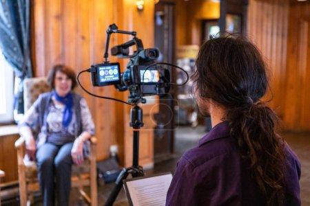 Photo pour Un homme est vu assis derrière l'équipement professionnel de fabrication de film, comme il enregistre une dame plus âgée parlent de la diversité et de l'âge dans un environnement de col blanc. - image libre de droit
