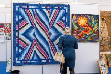 Photo pour Krasnoïarsk, la région de Krasnoïarsk / Rf-27 octobre 2018: une femme regarde un patchwork accroché sur un mur dans la salle d'exposition à la foire traditionnelle ville traditionnelle de l'artisanat. - image libre de droit