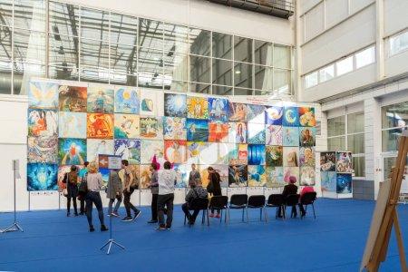 Photo pour Krasnoïarsk, la région de Krasnoïarsk / Rf-27 octobre 2018: les gens regardent peintures sur le thème «Ange de la paix» dans le hall d'exposition à la foire populaire d'urbaine traditionnelle de l'artisanat. - image libre de droit
