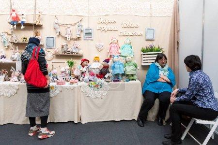 Photo pour Krasnoïarsk, la région de Krasnoïarsk / Rf-27 octobre 2018: femme se tient sur le stand avec des jouets à côté de l'assise artisane Tatyana Koval lors d'une foire populaire ville traditionnelle d'art populaire, artisanat. - image libre de droit