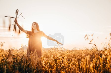 Photo for Happy woman in green dress stands smilling in wheat field with shining sun - Royalty Free Image