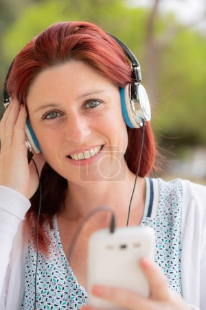 Photo for Portrait of an attractive smiling redhead woman listening to music on her phone with a headset with greenery in the background - Royalty Free Image