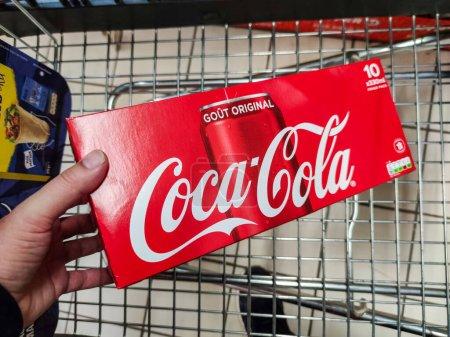 Photo pour Puilboreau, France - 14 octobre 2020 : Gros plan de l'homme achetant à la main une boisson gazeuse Coca Cola et plaçant un paquet de coca cola dans son panier de supermarché - image libre de droit