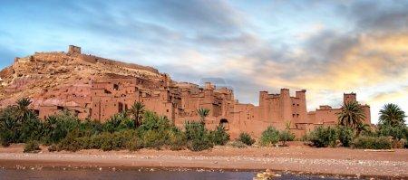 Photo pour Ksar d'Ait Ben Haddou (Ait Benhaddou) est une ville fortifiée (ighrem) sur l'ancienne route caravane entre le Sahara et Marrakech au Maroc. Patrimoine mondial de l'UNESCO. Panorama au coucher du soleil désert - image libre de droit